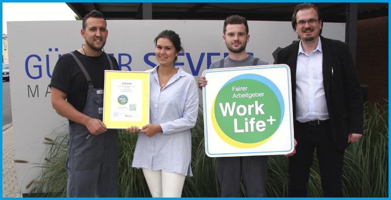 Katharina Günther freut sich mit einigen Beschäftigten und Sebastian Baacke von FairnessRatings über die Auszeichnung mit dem Work Life Plus Arbeitgebersiegel