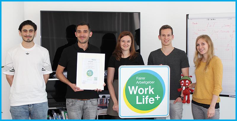 Thomas Faß, Tanja Zastrow und weitere Beschäftigte von Alter Solutions Deutschland freuen sich über die Auszeichnung mit dem s fairer Arbeitgeber mit dem Work Life Plus Arbeitgebersiegel